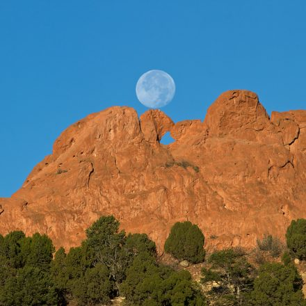 The full moon setting on the rock formation of Siamese Twins at Garden of the Gods in Colorado Springs, Colorado