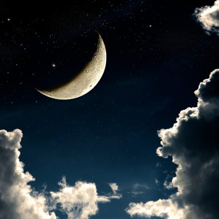 A fantasy of night sky cloudscape with stars and a crescent moon overlaid vintage color toned